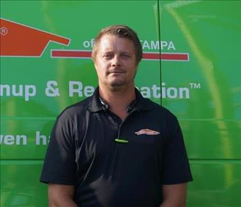 SERVPRO Crew Chief Taylor is shown, male in front of green truck
