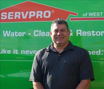 Mike the General Manager is shown in front of a green SERVPRO van, male employee